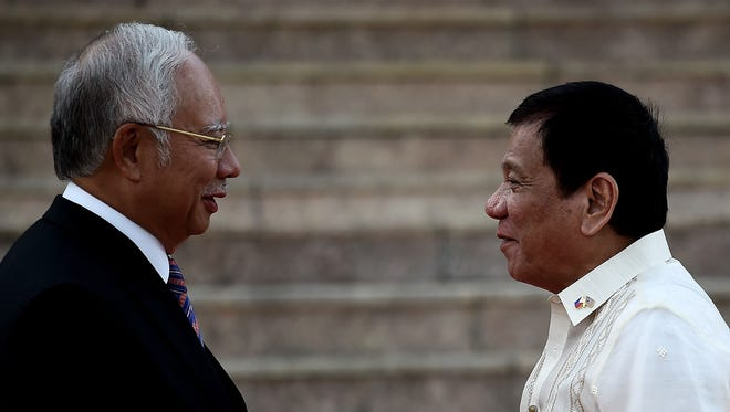 Malaysia's Prime Minister Najib Razak (left) welcomes Philippine President Rodrigo Duterte during a ceremony at the prime minister's office in Putrajaya on Nov. 10, 2016.