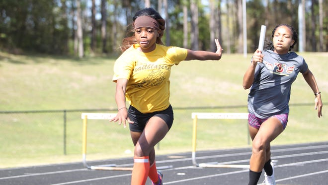 Florida High's Jacquell Lewis and Adrianna Mitchell practice baton passes for the 4x100 relay during a practice on Wednesday.