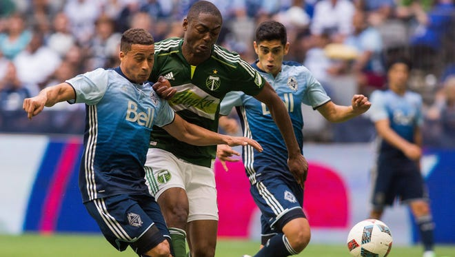 Vancouver Whitecaps' Erik Hurtado, left, fights for the ball against Portland Timbers' Fanendo Adi, center, during the second half of an MLS soccer game in Vancouver, British Columbia, Saturday, May 7, 2016.