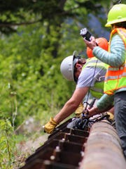Crews reinstall removable guardrails on cleared sections of Going-to-the-Sun Road.