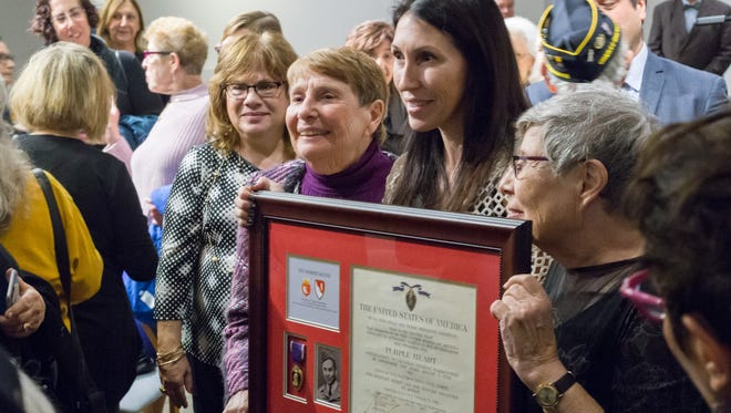 Mathis family members Faye Menczer Asher, Kris Mathis, and Gloria Zeitak pose with Tech 5th Grade Robert Mathis's Purple Heart Certificate during a Reuniting Ceremony at the Holocaust Memorial Center in Farmington Hills, Michigan, on Nov 13, 2016.