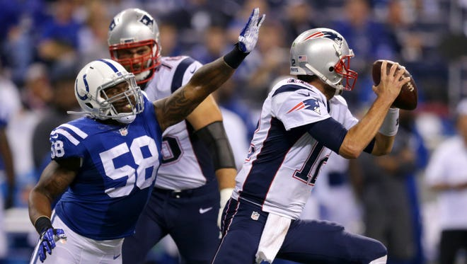 Indianapolis Colts outside linebacker Trent Cole (58) rushes in to try to strip the ball away from New England Patriots quarterback Tom Brady (12) during second half action of an NFL football game Sunday, Oct. 18, 2015, at Lucas Oil Stadium. Patriots won 34-27.
