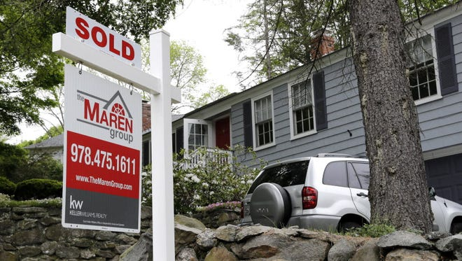"Photo shows a ""Sold"" sign in front of a house in Andover, Mass."