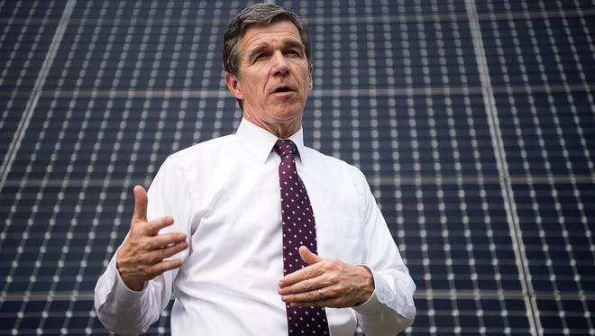 Standing in front of the Southern Alliance for Clean Energy's array of solar panels, N.C. Attorney General Roy Cooper talks about his support for renewable energy Wednesday. The political arm of the group endorsed Cooper at an event at its office just north  of downtown.