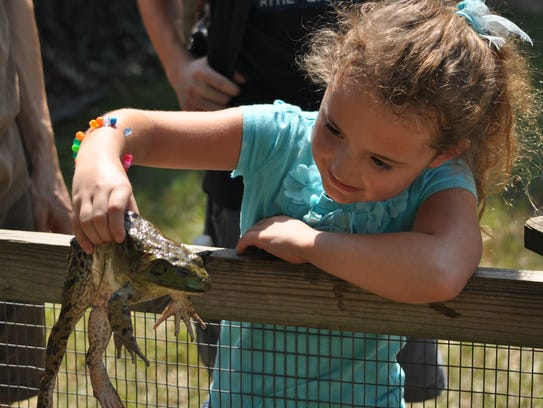 Lauren Girouard holds a frog Saturday at the Louisiana