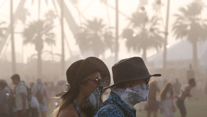 A couple walks through the grounds wearing hats and bandanas over their faces as winds kicked up dust during the 2014 Coachella Valley Music and Arts Festival in Indio. Festival officials on Thursday warned festival attendees of impending high winds in the region.