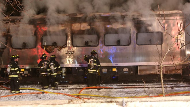 Firefighters work at the scene of an accident where a train crashed into an SUV in Valhalla, N.Y. Tuesday.