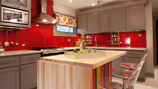 Designer Meg Caswell painted the walls red then added a clear glass cover to create a chic, vibrant backsplash.