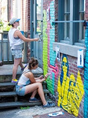 Emily Herr, top, and Sarah Apple paint a mural in the alley behind Battery Street Jeans in Burlington on Tuesday, August 1, 2017.  Herr has travelled to a number of cities painting murals that express positive images of women and girls.