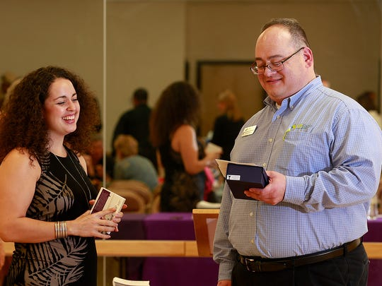 James Knight, right, of U.S. Eagle Federal Credit Union, talks to Alisha Chavez of the New Mexico Coalition Against Domestic Violence after receiving the Community Hero Award on Thursday during a ceremony at the Bonnie Dallas Senior Center in Farmington.