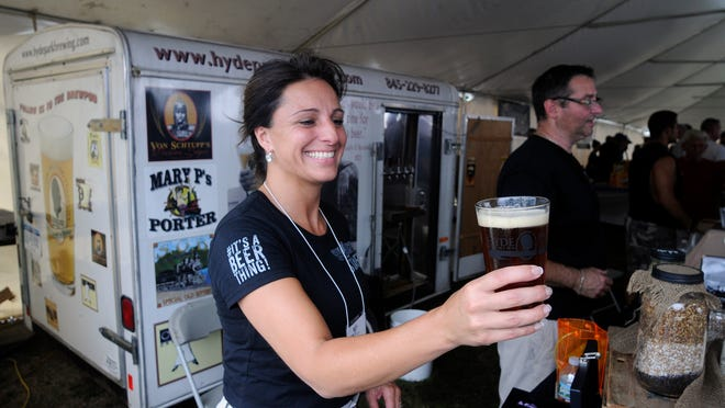 Angela LoBianco-Barone of the Hyde Park Brewing Company hands over a freshly-poured pint on Saturday to a customer at the Hudson Valley Food and Wine Fest in Rhinebeck.
