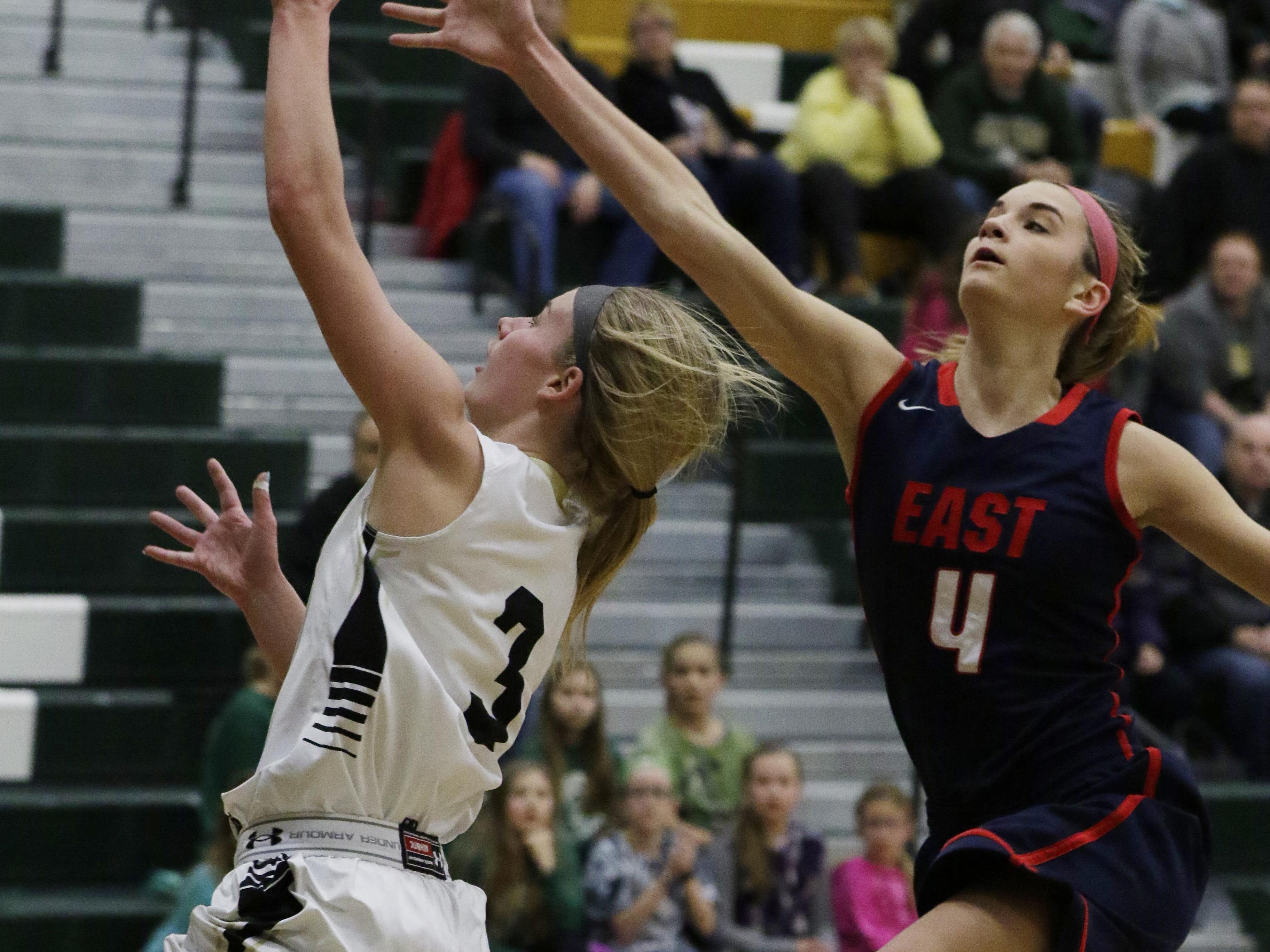 Oshkosh North's Ashley Wissink puts up a shot over Lexie Schneider of Appleton East on Friday in Oshkosh.