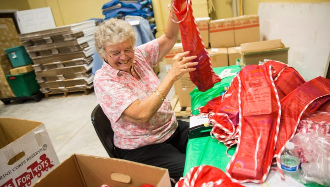 Julie Egenberg, who has been a Toys For Tots volunteer for twelve years, stuffs stockings with toy cars at the Salvation Army Christmas Toy Shop in Naples on Tuesday, Dec. 5, 2017.