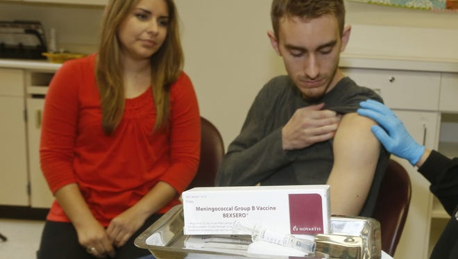 Meningococcal meningitis survivor and vaccination advocate Leslie Meigs looks on as her brother Andrew, a college student in Texas, receives a meningococcal group B vaccine in January 2015.