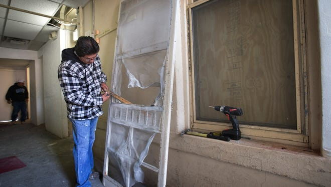 Workers repair the apartments at 219 W. Overland after the bulding's owner failed to comply with a December repair order. The repairs including providing heat for the tenants, roof repairs and fumigation to remove bed bugs.