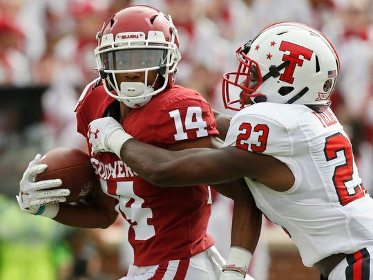 Texas Tech defensive back Damarcus Fields (23) reaches in to tackle Oklahoma wide receiver Charleston Rambo (14) in the first quarter of an NCAA college football game in Norman, Okla., Saturday, Sept. 28, 2019. (AP Photo/Sue Ogrocki)
