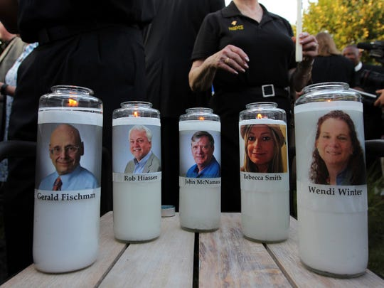 Photos of five journalists adorn candles during a vigil across the street from where they were slain in their newsroom in Annapolis, Md., Friday, June 29, 2018. Prosecutors say Jarrod W. Ramos opened fire in the Capital Gazette newsroom. (AP Photo/Jose Luis Magana)