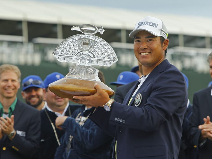 Hideki Matsuyama hoists the winners trophy following
