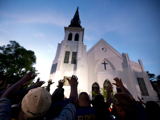 Omega Psi Phi fraternity members lead a prayer group outside Emanuel AME Church  in Charleston, South Carolina, on June 19, 2015.