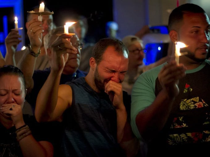 Supporters of the gay community gathered at TattleTails in Port St. Lucie on Sunday for a candlelight vigil. 'I have friends and have been to the club, so I kind of visualized it my head when it happened,' said Rafael Gomez (center), of Port St. Lucie, who was attending with his boyfriend Joshua Serrano (right), also of Port St. Lucie. 'I'm a performer, so I was just thinking of the performers that were performing (at Pulse).' Rachael Tilman, of Port St. Lucie, stands at left.