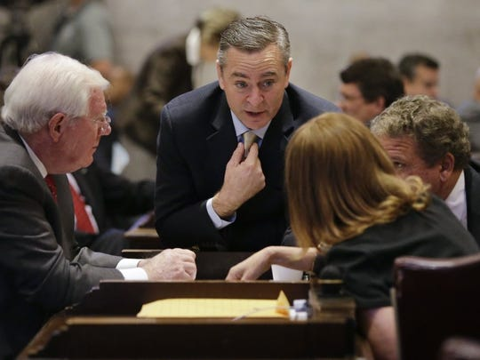 Rep. Glen Casada, R-Franklin, center, talks with other members of the House including Rep. Charles Sargent, R-Franklin, left, during a debate on whether to override Gov. Bill Haslam's veto of a bill seeking to make the Bible the state's official book, Wednesday, April 20, 2016, in Nashville, Tenn. The House voted not to override the veto.