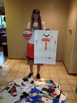 Katie McWilliams stands with recruiting mail from various colleges around the country. McWilliams committed to playing basketball for Oregon State.