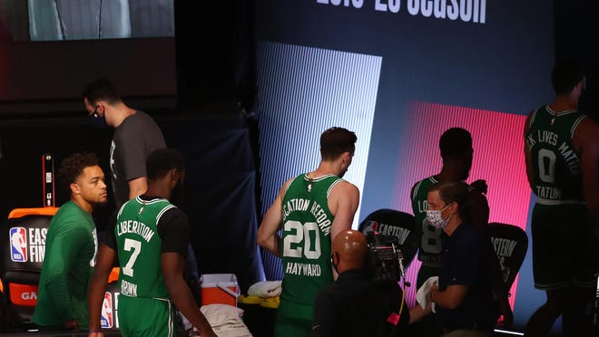 Celtics guard Jaylen Brown (7), forward Gordon Hayward (20) and their Boston teammates leave the court after a loss to the Miami Heat in Game 4 of the Eastern Conference finals on Wednesday night. Game 5 is Friday at 8:30 p.m.