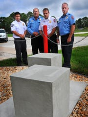 KSC Batallion Chief Charles Lombard, firefighter/driver Thomas Van Horn, KSC Fire Chief Rick Anderson and KSC fighter Lt. James Dumont stand by the concrete setting for the 7 foot I-beam from the World Trade Center.