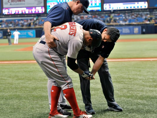 Boston Red Sox manager John Farrell, left and assistant athletic trainer Masai Takahashi, right, check on Xander Bogaerts after he was hit by a pitch from Tampa Bay Rays starter Jake Faria during the first inning of a baseball game Thursday, July 6, 2017, in St. Petersburg, Fla. (AP Photo/Steve Nesius)