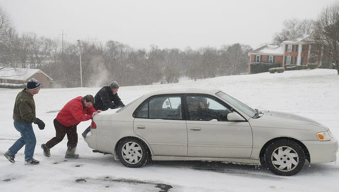 John Bass, Kyle Piccirilli and Jud Haynie  push car up an icy hill in Brentwood, Tn.