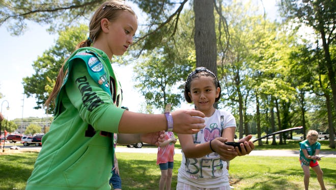 Kiralee Schier of Neillsville, 10, right, passes a ladle of water to Ashley Fuller of Wisconsin Rapids, 10, during a water relay for the Let's Keep It Clean patch program for Girl Scouts in Marshfield.