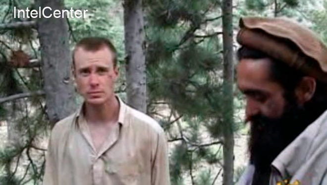 """FILE - This file image provided by IntelCenter on Dec. 8, 2010, shows a frame grab from a video released by the Taliban containing footage of a man believed to be Bowe Bergdahl, left.  Saturday, May 31, 2014, U.S. officials say Bergdahl, the only American soldier held prisoner in Afghanistan has been freed and is in U.S. custody. The officials say his release was part of a negotiation that includes the release of five Afghan detainees held in the U.S. prison at Guantanamo Bay, Cuba. (AP Photo/IntelCenter, File)  MANDATORY CREDIT: INTELCENTER; NO SALES; EDS NOTE: """"INTELCENTER"""" AT LEFT TOP CORNER ADDED BY SOURCE"""