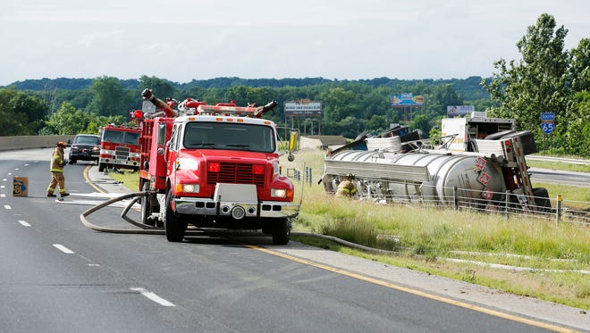 Firefighters respond after a tanker hauling heptane overturned in the southbound lane of I-65 Friday, July 3, 2014, just south of the Ind. 43 exit near Battle Ground. Sgt. Kim Riley of Indiana State Police said traffic in both lanes of I-65 would be closed until the highly flammable material can be cleaned up.