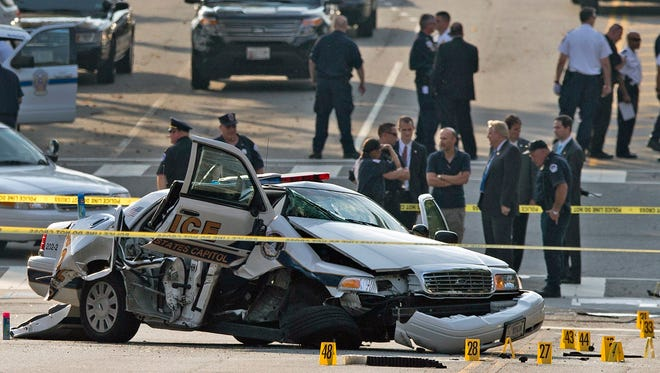 A damaged Capitol Hill police car is surrounded by crime scene tape after a car chase and shooting in Washington on Oct. 3, 2013. Police shot and killed 34-year-old Miriam Carey, of Stamford, Conn., after a car chase that began when Carey tried to breach a barrier at the White House.