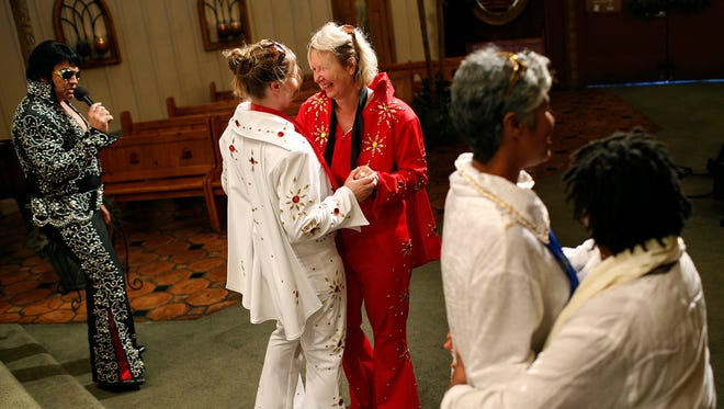 In this July 19, 2014 file photo, Sari Van Poelje, in red, dances with Katharina during their commitment ceremony given by Elvis tribute artist Michael Conti, left, at the Viva Las Vegas Wedding Chapel in Las Vegas. Gay marriage isn't legal in Nevada. The same-sex marriage debate returns Monday Sept. 8, 2014, to the San Francisco federal appeals court that has already issued two significant rulings in support of gay weddings. The 9th U.S. Circuit Court of Appeals will consider separate lawsuits stemming from gay marriage bans in Idaho, Nevada and Hawaii.