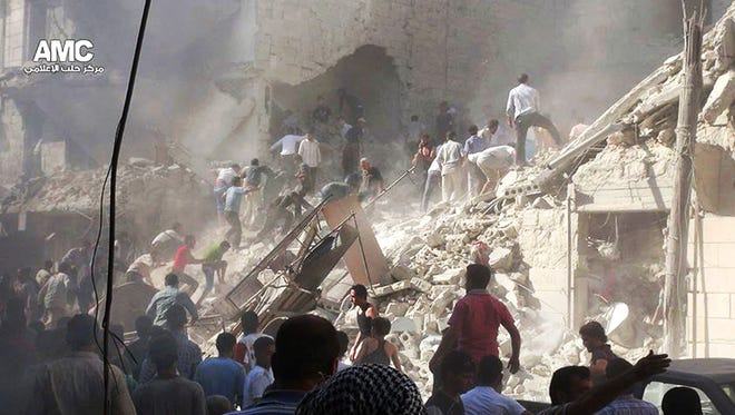 Syrians inspect the rubble of damaged buildings from heavy shelling by Syrian government forces in Aleppo on Monday.