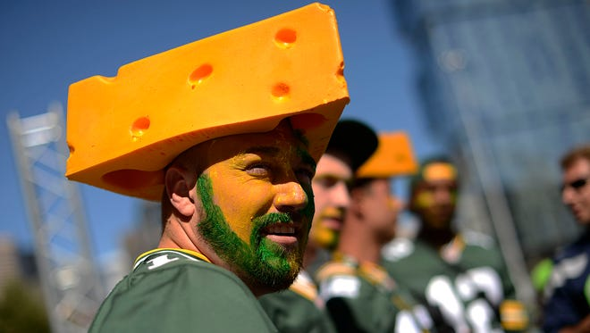 Andrew Ferguson, from Virginia, sports a cheesehead and face paint as he wanders around CenturyLink Field in Seattle.