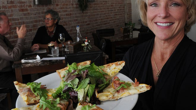 Diane Laird, co-owner of the Cork restaurant, displays Meyer Lemon and Proschuitto Flatbread. It is her favorite dish.