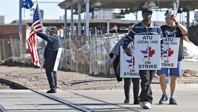 Amalgamated Transit Union Local 1433 bus drivers picket outside the Valley Metro bus yard in south  Phoenix on Wednesday, Jan. 13, 2016.