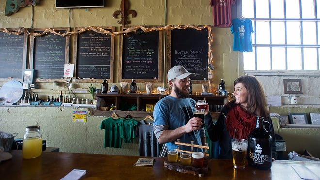 Owners Joe Dinan and Lisa McDonald cheers each other with their own brews Feb. 26, 2016 at Sanctuary Brewing Company on First Avenue East in Hendersonville.