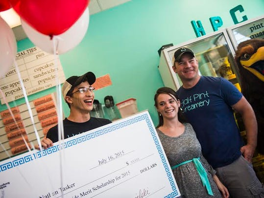 Nathan Tasker, 18, laughs after officials from HACC's Gettysburg campus surprised the Half Pint Creamery employee with a two-year scholarship while he was at work Thursday. Tasker was posing for pictures with his boss, Half Pint Creamery owner Trish Motter and Travis Sentz.