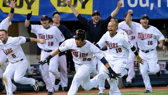 Minnesota Twins' Carlos Gomez (22) scores the game-winning run as his teammates follow during the 12th inning of a baseball game against the Detroit Tigers on Tuesday, Oct. 6, 2009, in Minneapolis. The Twins won 6-5 to take the AL Central title. (AP Photo/Jim Mone)