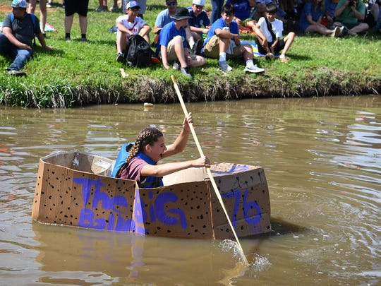 Aliya Corona squeals as water begins leaking into her cardboard boat Wednesday morning during the 12th Annual Barwise Cardboard Boat Float at Sikes Lake.