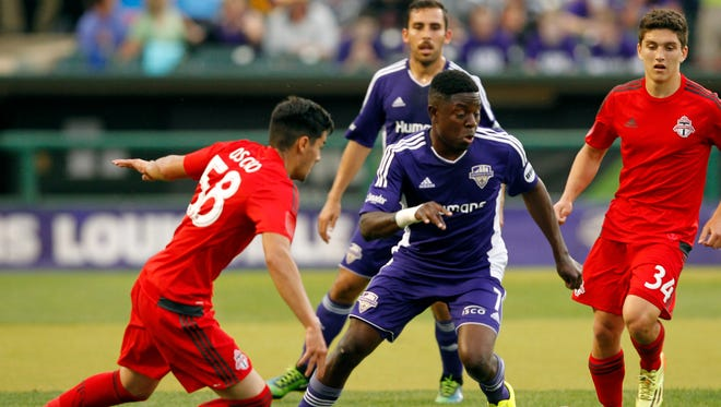 Louisville FC's Kadeem Dacres (7) battles pressure from Toronto FC's Jonathan Osorio (58) during their game at Louisville Slugger Field in Louisville, Kentucky.         May 16, 2015