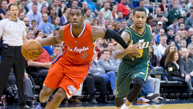Los Angeles Clippers guard Chris Paul (3) dribbles the ball around Utah Jazz guard Trey Burke (3) during the first half at EnergySolutions Arena.