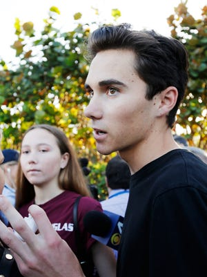 Marjory Stoneman Douglas High School student David Hogg, left, walks to class Wednesday for the first time since a former student opened fire there.  He's become a leading voice in a student-led movement to curb gun violence.
