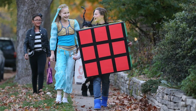 Dressed as a Rubix Cube Kobie Long, 12, and her friend Erin Martin, 13, walk through a Des Moines neighborhood enjoying the Beggar's Night festivities on Thursday, Oct. 30, 2014, in Des Moines, Iowa.