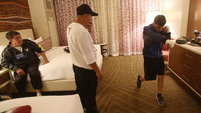 From left, Lee Espinoza and Marcos Caballero keep a close eye on the last tuneups from Randy Caballero's technique in his hotel room at the Manday Bay in Las Vegas, Nevada in preparation for his title defense against Lee Haskins of England on November 21, 2015 on the Canelo-Cotto undercard.