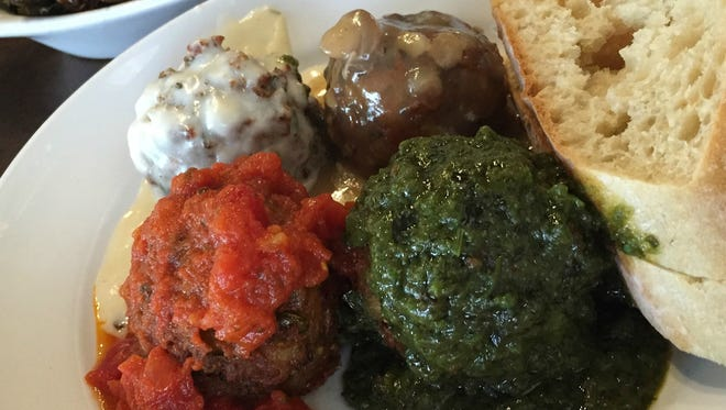 An Italian flag meatball combo at Mimi Blue featuring garlic cream, spicy Bolognese, spicy cilantro and mushroom gravy.