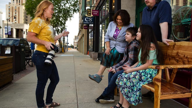 Photographer Kristi Mitchell arranges Wild Rose business owners Monica Zanetti, Jeremy Reed and their children Nicholas and Jackie on a bench in front of their store on South Sixth Street in Springfield, Ill., during a portrait session Thursday, May 7, 2020. Mitchell is photographing one small business a day to bring attention to how they've been affected by the COVID-19 related business closures.